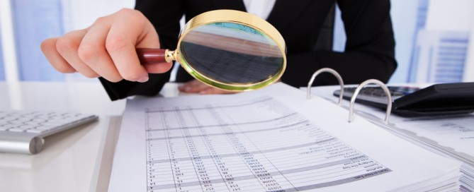Midsection of young businesswoman scrutinizing bills with magnifying glass at office desk